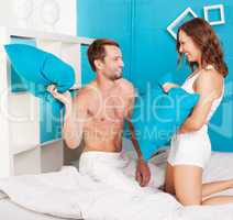 young couple having fun making pillows fight.