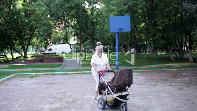 Grandmother walks with her grandson in the yard