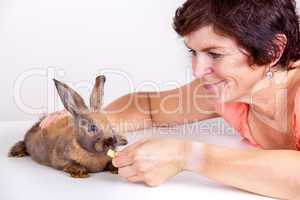 Young woman feeding rabbits