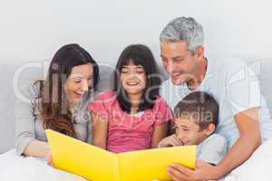 Family looking together at their photograph album in bed