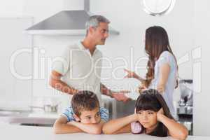 Unhappy siblings sitting in kitchen with their parents who are f
