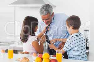 Children fixing their fathers tie in the kitchen