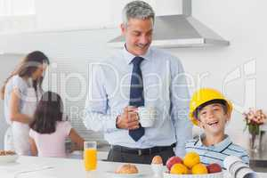 Funny little boy wearing fathers hardhat during breakfast
