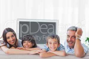Family in sitting room smiling at camera