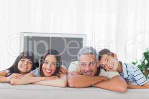 Cute family in sitting room smiling at camera