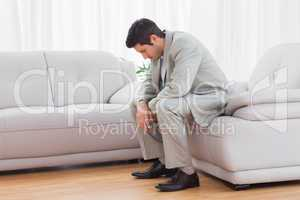 Unhappy buinessman sitting on sofa lowering his head