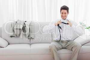 Smiling businessman sitting on sofa loosening his tie