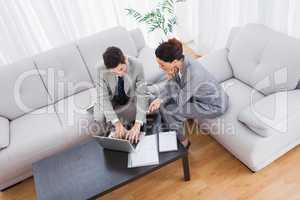 Colleagues working together sitting on sofa and using laptop