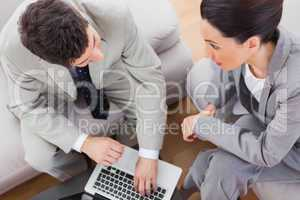 Coworkers talking and using laptop sitting on sofa