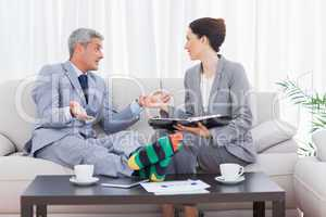 Funny businessman wearing stripey socks and talking with his col