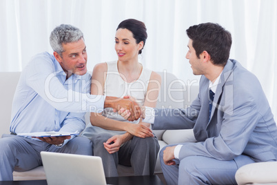 Salesman closing a deal with a smiling couple
