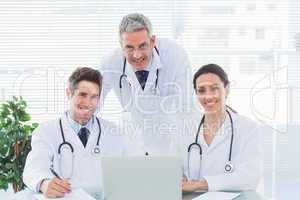 Team of doctors working together with their laptop looking at ca