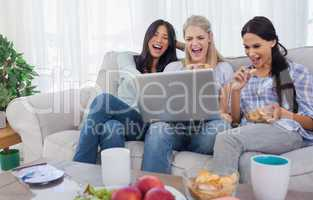 Smiling friends looking at laptop together and eating cookies