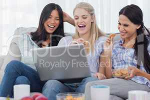 Laughing friends looking at laptop together and eating cookies