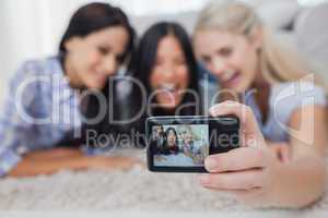 Friends lying on floor and taking a self picture