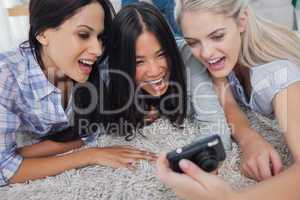 Friends lying on floor and looking at digital camera