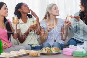 Friends drinking white wine and chatting during party