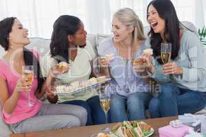 Friends drinking white wine and sharing cupcakes at party