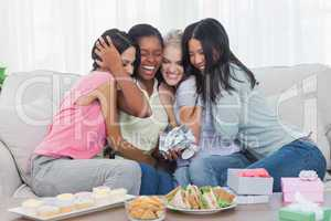 Friends offering gifts and hugging woman during party