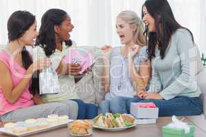 Friends offering gifts to woman during party