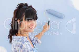 Pretty woman painting wall blue and smiling at camera