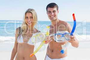 Attractive couple showing snorkels and goggles to camera
