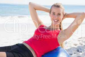 Fit blonde doing sit ups on exercise ball