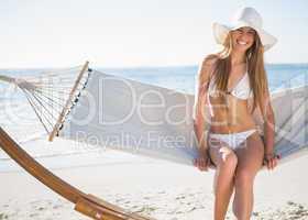 Pretty blonde wearing bikini and sunhat sitting on hammock and s