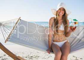 Pretty blonde wearing bikini and sunhat sitting on hammock with
