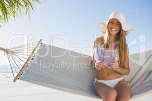 Smiling blonde wearing sunhat sitting on hammock holding book