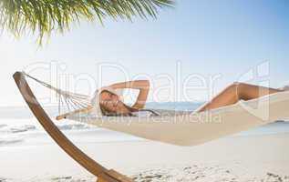Woman wearing sunhat and bikini relaxing on hammock smiling at c