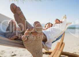 Close up of sandy feet of couple in a hammock