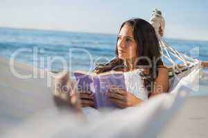 Woman lying on hammock holding book and thinking