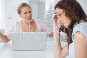 Unhappy woman thinking while her friend is interrogating her