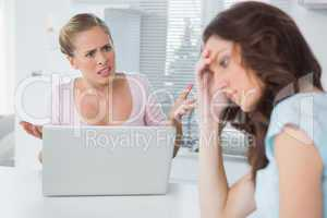 Unhappy woman thinking while her friend is getting angry at her