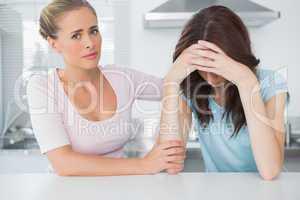 Understanding woman comforting her upset friend