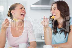 Laughing friends eating cake and having coffee