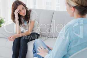 Upset woman sitting on the couch and looking at therapist