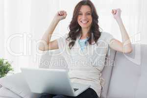 Cheering woman with laptop on her knees
