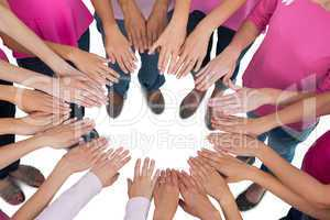 Hands joined in circle wearing pink for breast cancer