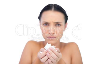 Sick natural brunette holding tissue
