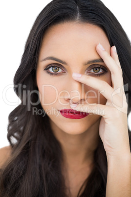 Dark haired model with red lips hiding her face