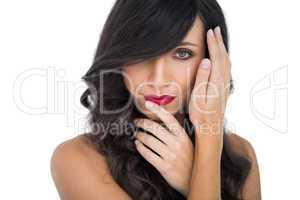 Glamorous brunette posing finger on her red lips