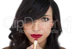 Glamorous brunette applying red lipstick