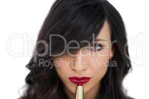 Sensual brunette applying red lipstick