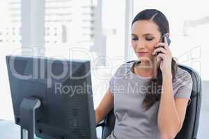 Dark haired businesswoman having a phone conversation