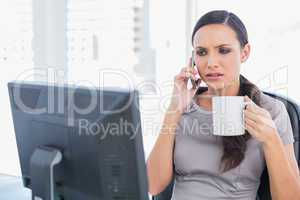 Frowning businesswoman holding coffee and answering phone