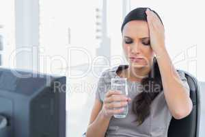 Attractive secretary with headache holding water and touching he