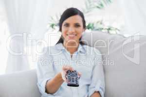 Cheerful attractive brunette changing tv channels