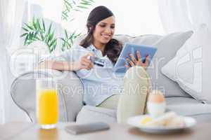 Cheerful brunette buying online while having breakfast